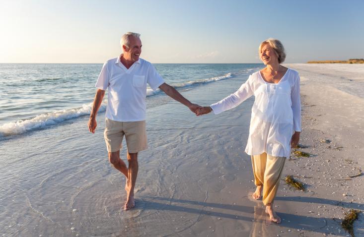 Happy Retirees Walking on the Beach