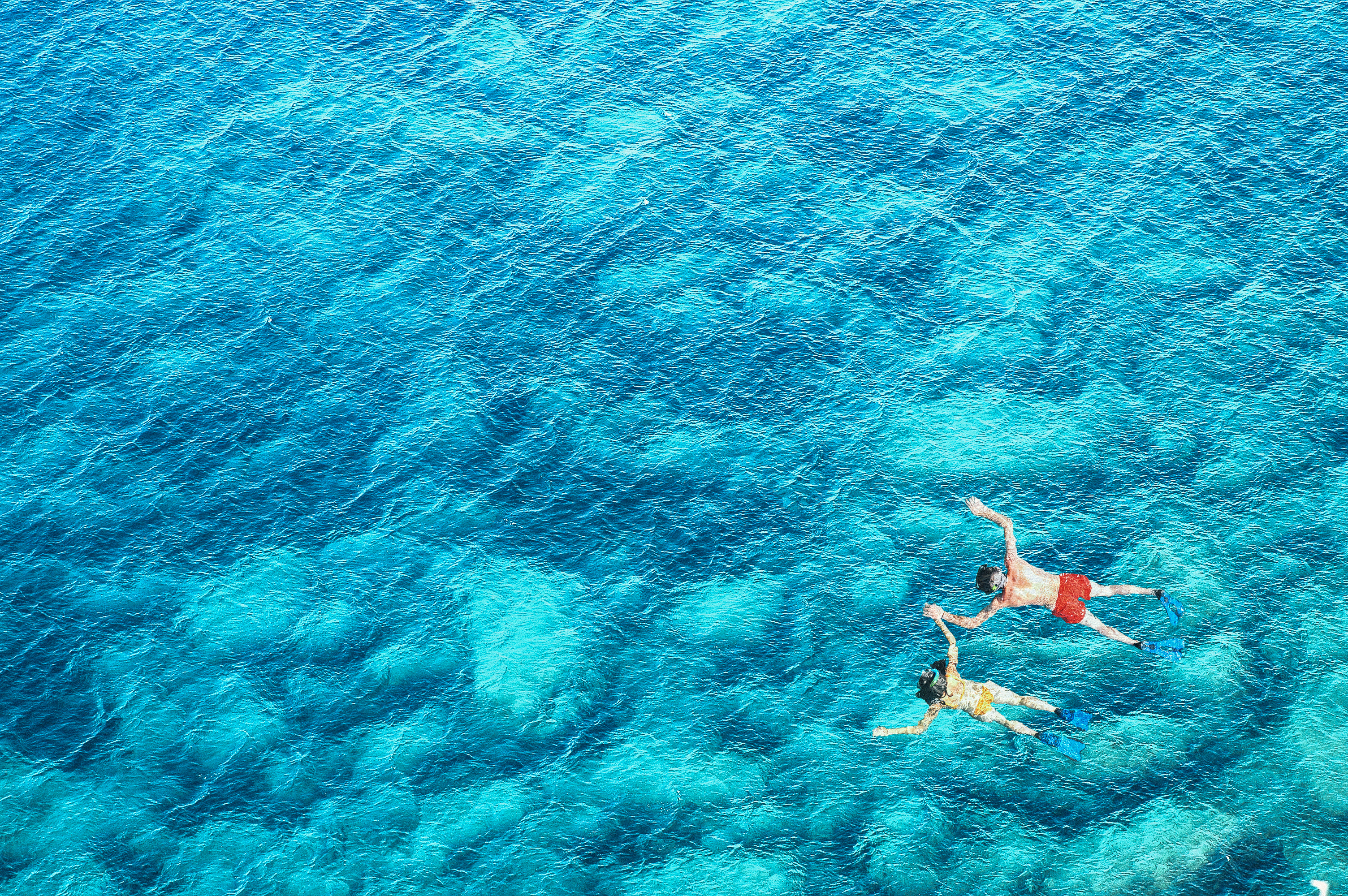 above-view-of-couple-snorkeling-in-blue-sea-water--PK329QS