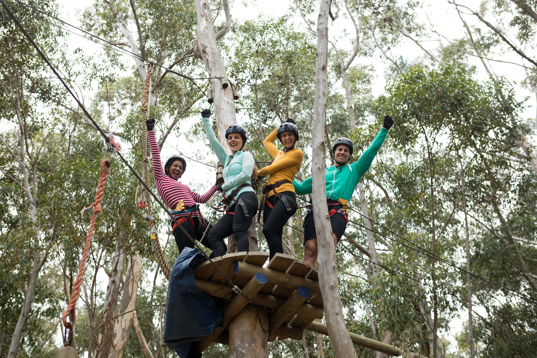 friends-enjoying-zip-line-adventure-in-park